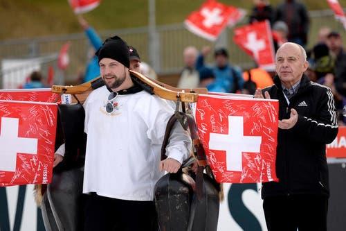 Bundesrat Ueli Maurer klatscht und ein Schweizer Fan läutet die Glocken. (Bild: Keystone / Sigi Tischler)