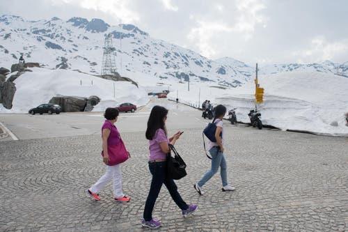 Die ersten Touristen spazieren neben den Schneemassen auf dem am 13. Mai eröffneten Gotthardpass. (Bild: DAVIDE AGOSTA)