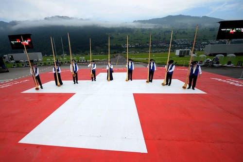 Die Ruhe vor der Enthüllung: Alphornbläser positionieren sich auf einer riesigen Schweizer Flagge für ihren Auftritt. (Bild: Keystone)