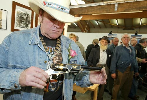 Angy Burri besichtigt am 2. April 2004 eine seiner Lieblingspistolen, die Colt Walker 1847, anlässlich der Eröffnung der Waffen-Sammlerbörse auf der Luzerner Allmend. (Bild: Keystone)