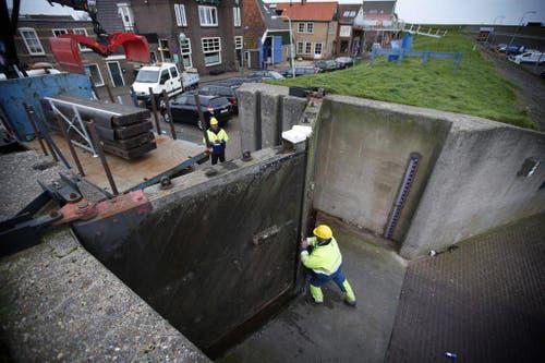 Im niederländischen Den Oever schliessen Arbeiter vorsichtshalber die Tore der Deiche. (Bild: Keystone)