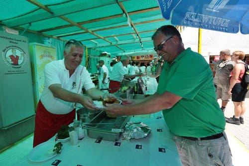 An der 1. August-Feier in Beckenried. Wisi Imholz (links) übergibt Peter Mathis die Fischspezialität. (Bild: Roger Zbinden / Neue NZ)