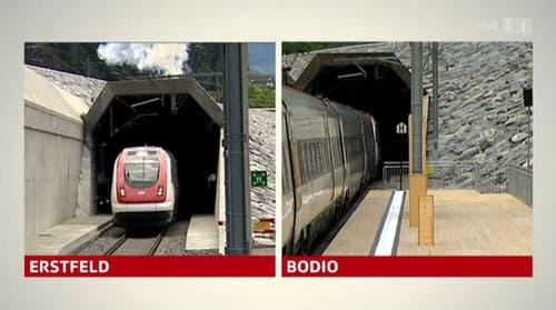 Fast synchron: Die Eröffnungszüge fahren aus dem Tunnel. (Bild: Alptransit Livestream)