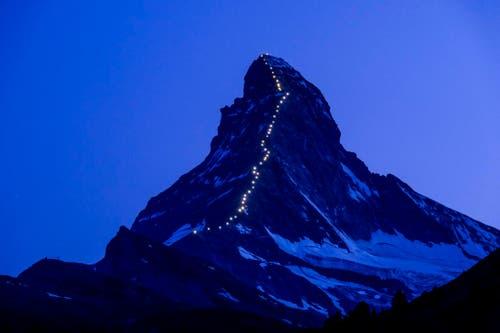8. Juli: Zeitschaltuhren sind schuld. Die Lichterkette am Matterhorn in Zermatt, die den Weg nachzeichnet, den die Erstbesteiger vor 150 Jahren genommen haben, wird eine Woche zu früh aktiviert. (Bild: Keystone / Jean-Christophe Bott)