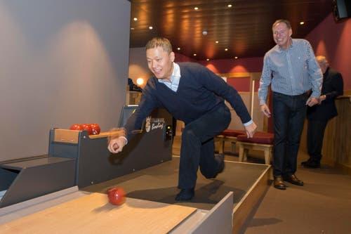 Yunfeng Gao zeigt, wie Bowling gespielt wird. Rechts im Bild: Toni Eberli, Verwaltungsratspräsident der Eberli Sarnen AG. (Bild: Keystone / Urs Flüeler)