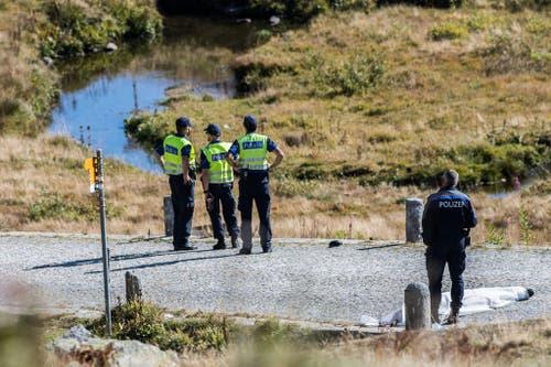 Polizisten und Forensiker stehen in der Nähe der Absturzstelle. (Bild: Keystone)