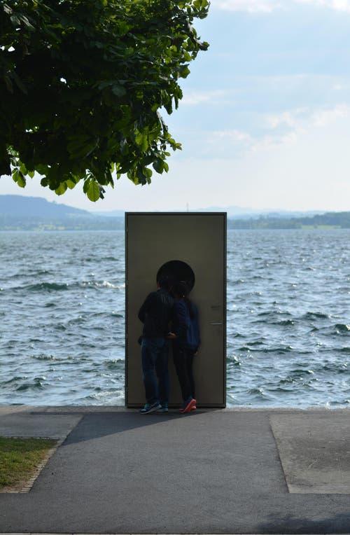 Es sind alle gespannt und schauen durch das kleine Fenster, diskutieren, fotografieren und wundern sich über die «Tür ins Nichts». (Bild: Leser Balz Auf der Maur)