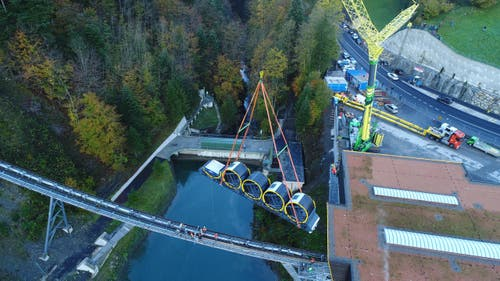 Blick aus der Luft: Der erste von zwei Wagen wird auf das Trassee gehievt (12.10.2017) (Bild: PD)