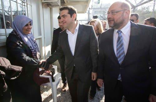 Der griechische Premierminister Alexis Tsipras, Mitte, und EU-Parlamentspräsident Martin Schulz, begrüssen eine Frau im Flüchtlingslager in Moria. (Bild: EPA/Andrea Bonetti)
