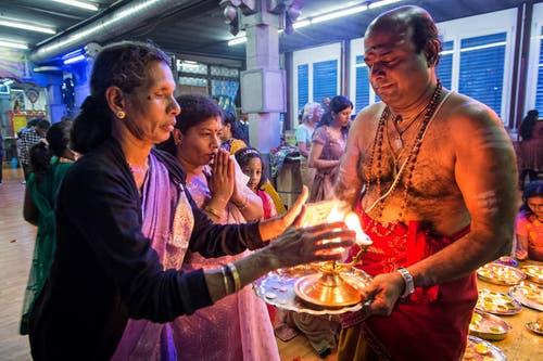 14. April: Die Tamilen in der Zentralkschweiz feiern an diesem Sonntag Neujahr. In Root geht Priester Sasitharan Ramakrishna Sarma nach dem Gebet mit dem Feuer um - und spendet den Gläubigen damit den Segen. (Bild: Remo Nägeli / Neue LZ)