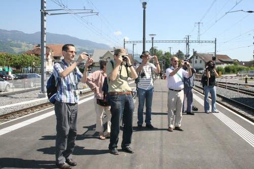 Die historische Dampflok ist die Attraktion am Jubiläum. Der Tross an Fotografen von Fachzeitschriften und Eisenbahnfreunden hat sich zur Einfahrt positioniert. (Bild: Marion Wannemacher / Neue OZ)