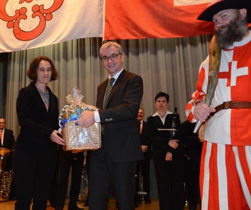 Als Geschenk von der Gemeinde gibt es Honig und Kernser Teigwaren - Gemeinde-Vizepräsidentin Sonnie Burch-Chatti gratuliert dem Neugewählten. (Bild: Romano Cuonz / Neue NZ)