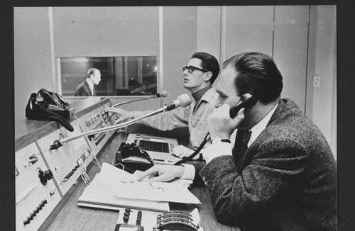 1962: Tagesschau-Regie. Von hier aus wird die ganze Sendung gelenkt, werden Filme und Fotos dazwischengeschaltet und dem Sprecher nach Redaktionsschluss eingegangene wichtige Meldungen übermittelt. Im Hintergrund sieht man durch eine Glaswand in die Kabine des Sprechers, hier Erich Gysling. (Bild: SRF)