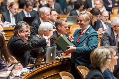 Beat Flach, GLP-AG, links, gibt seinen Stimmzettel in die Urne, welche ihm Ratsweibelin Nathalie Radelfinger hinhält. (Bild: KEYSTONE / LUKAS LEHMANN)