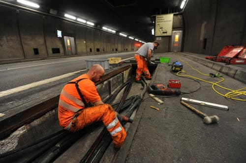 Zwei Mitarbeiter ziehen ein neues Kabel für das neue Videoüberwachungssystem ein. (Bild: Urs Hanhart / Neue UZ)