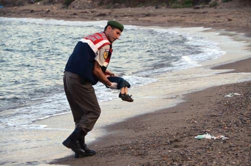 2. September: Dieses Foto wird zum Symbolbild des Flüchtlingsdramas. Ein Helfer trägt den leblosen Körper des dreijährigen Aylan Kurdi, der bei der Flucht übers Meer ertrunken und an den Strand der griechischen Insel Kos gespühlt worden ist. (Bild: Keystone/AP Photo/DHA)