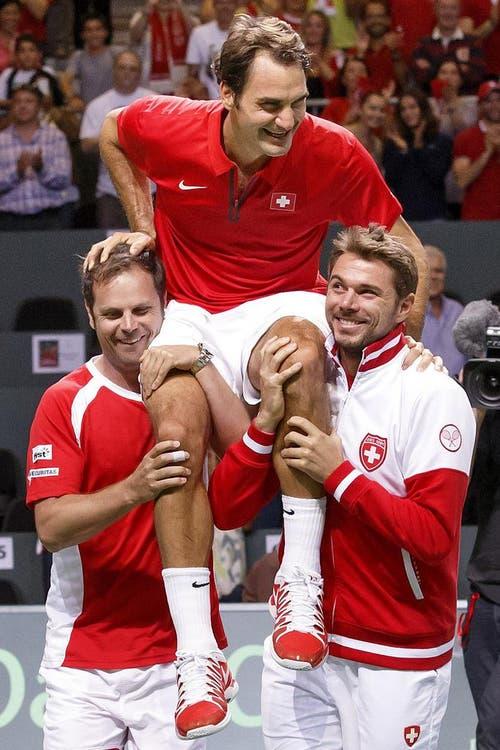 Roger Federer wird von Teamcaptain Severin Lüthi (links) und Stan Wawrinka in die Höhe gestemmt. (Bild: Keystone)