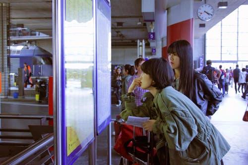 Touristinnen aus Asien kämpfen sich durch die Abfahrtstabelle. (Bild: Christian Volken / luzernerzeitung.ch)