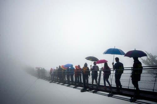 Eine Gruppe Menschen überquert die neu eröffnete Hängebrücke in der Nähe von Monte Carasso im Tessin. Die Hängebrücke ist 270 Meter lang und hat eine maximale Höhe von 130 Metern. (Bild: Keystone / Ti-Press / Samuel Golay)