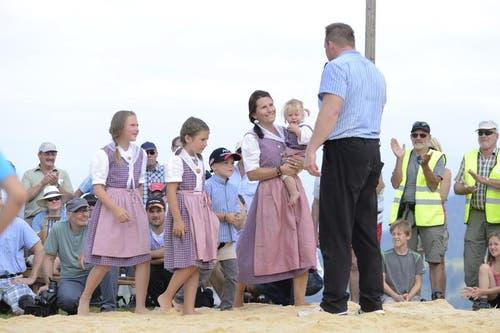 Adi Laimbacher verabschiedet sich nach seinem letzten Schwing-Kampf von der Schwinger-Bühne und wird zusammen mit seiner Frau und seinen Kindern in Tracht vom Publikum gefeiert. (Bild: Dominik Wunderli / Neue LZ)
