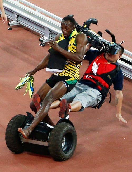 Ein Kameramann fährt den jamaikanischen Sprintstar Usain Bolt bei den Weltmeisterschaften in Peking über den Haufen (27. August). (Bild: EPA / Rolex dela Pena)