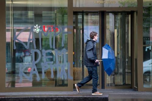 """Zürich: Ein Mann läuft vor einer versprayten Fassade der UBS auf der """"Kampf dem Kapital"""" steht. (Bild: Keystone)"""