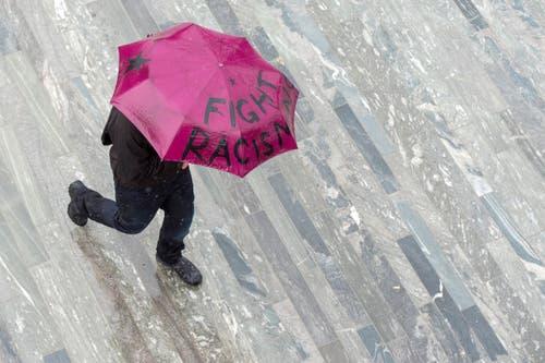 """Zürich: Ein Mann mit Schirm """"Fight Racsim"""" fotografiert am traditionellen 1. Mai-Umzug. (Bild: Keystone)"""