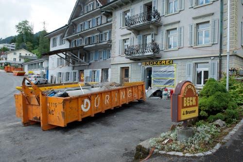 Die Verwüstung ist in Dierikon noch präsent. Beispielsweise bei der stark betroffenen Bäckerei Brunner. Was zu Bruch gegangen ist, landet nun im Container. (Bild: Dominik Wunderli (Neue LZ))