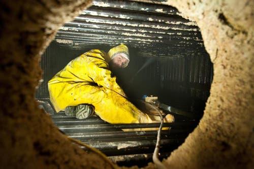 Kaminfeger Manuel Bürkli reinigt den bereits abgestellten Ofen mit dem Hochdruckreiniger. (Bild: Boris Bürgisser / Neue LZ)