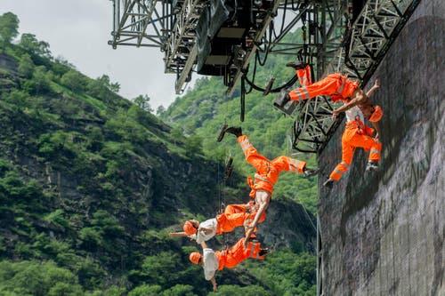 Artisten der Eröffnungsshow versetzen sich in das Leben gefährlich lebender Gotthard-Mineure: (Bild: Keystone/Ti-Press/Carlo Reguzzi)