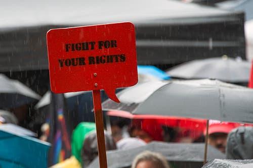 """Basel: Demonstranten mit Regenschirmen halten ein Schild hoch mit der Aufschrift """"fight for your rights"""". (Bild: Keystone)"""