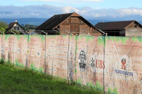 Die Gitterdrähte sind mit grossen Kunststoffplanen geschickt verdeckt. Die Auftritte der Sponsoren sind für einmal nicht in schreienden Farben gehalten, sondern schön in Holz- und Laubfarben eingelegt. Gerade deshalb fäll die Werbung auf. (Bild: Swiss Image / Andy Mettler)