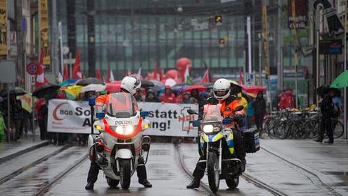 Basel: Polizisten auf Motorrädern begleiten bei strömendem Regen den Demontrationszug. (Bild: Keystone)