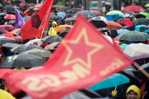 Zürich: Demonstranten verfolgen die Reden unter Regenschirmen auf dem Sechseläutenplatz. (Bild: Keystone)