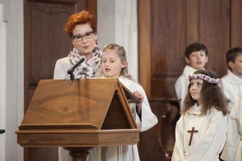Angeleitet von Katechetin Berta Christen begrüsst Michelle Venzin die Kirchgänger in Wolfenschiessen, während Samira Christen auf ihren Einsatz wartet. (Bild: Edi Ettlin)
