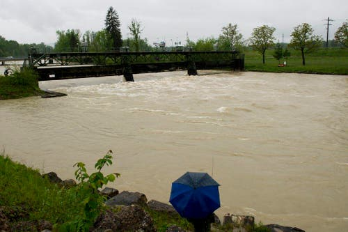 Zuschauer stehen am 1. Juni 2013 in Perlen am Wehr und blicken auf die hochwasserführende Reuss. (Bild: Keystone)