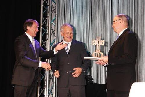 Bundesrat Johann Schneider-Ammann bekommt von Peter Murer und Gerhard Odermatt einen kleinen 'grossen Iheimisch-Schlüssel'. (Bild: André A. Niederberger / Neue NZ)
