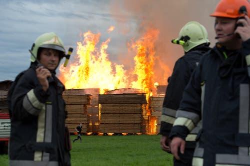 Feuerwehrleute koordinieren ihren Einsatz am Brandort in Urswil. (Bild: Dominik Wunderli / Neue LZ)