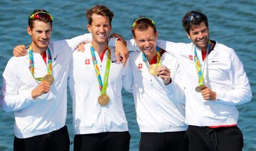 Sie tragen stolz die Goldmedaille: Das Schweizer Team mit Simon Schürch, Simon Niepmann, Lucas Tramer und Mario Gyr (von links). (Bild: EPA / Diego Azubel)