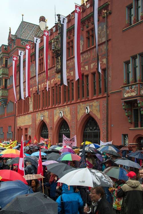 Basel: Demonstranten mit Regenschirmen versammeln sich bei strömendem Regen auf dem Marktplatz beim traditionellen 1. Mai-Umzug. (Bild: Keystone)