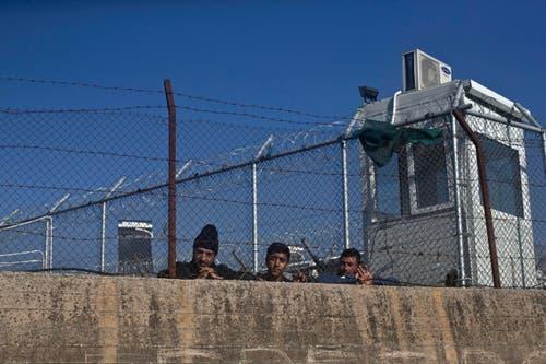 Drei Männer hinter den Mauern des Registrierungscamps Moria. (Bild: AP/Marko Drobnjakovic)