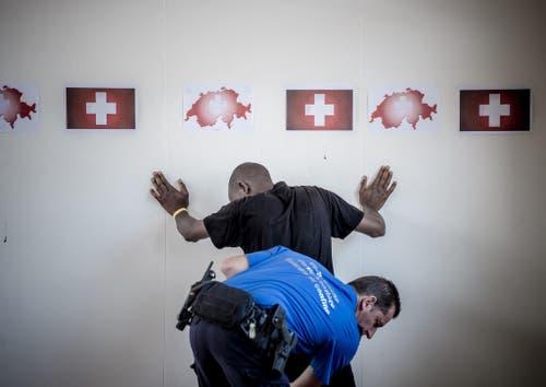 20. Juni: Ein Angehöriger des Grenzwachtkorps durchsucht am Zoll des Bahnhofs Chiasso einen Migranten. In den Sommermonaten sind überdurchschnittlich viele Asylsuchende in die Schweiz gelangt. Im Empfangs- und Verfahrenszentrum Chiasso kommt es deswegen zu Engpässen. (Bild: Keystone)