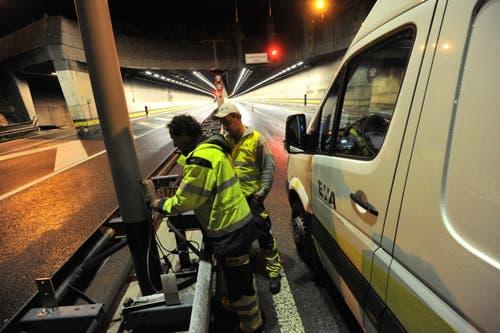 Zwei Mitarbeiter des Elektrizitätswerk Altdorf ziehen vor dem Gotthard-Tunnel ein Kabel ein. (Bild: Urs Hanhart / Neue UZ)