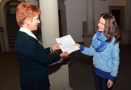 Eine Schülerin der 1. Klasse übergibt der Kantonsratspräsidentin Trix Dettling Schwarz 1054 Unterschriften, die an der Kantonsschule Alpenquai «gegen die Sparmassnahmen auf Kosten der Schüler/innen» gesammelt worden waren. (Bild: PD)