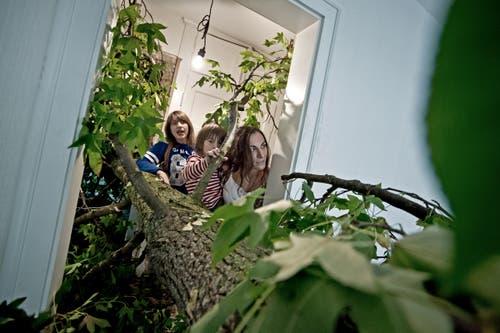 Ein 18 Meter langer Baumstamm hat quer in der Wohnung Platz gefunden. Bestaunt durch Nadja Bürgi (hinten) Amun Martin (5 Jahre mitte) und seine Mutter Fabienne Marti (vorne). (Bild: Pius Amrein / Neue LZ)