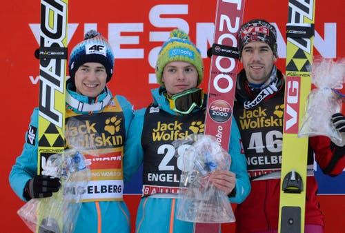 Kamil Stoch (links) und Jan Ziobra (Mitte) aus Polen sowie Andreas Bardal aus Norwegen stehen auf dem Podest nach dem ersten Springen am Samstag. (Bild: URS FLUEELER (KEYSTONE))