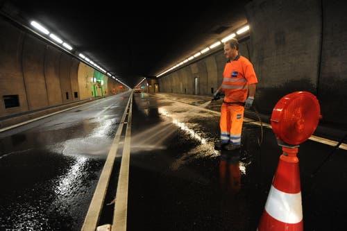 Nachdem die Tunnelwand in der Nische abgespritzt worden ist, wird die Strasse gereinigt. (Bild: Urs Hanhart / Neue UZ)