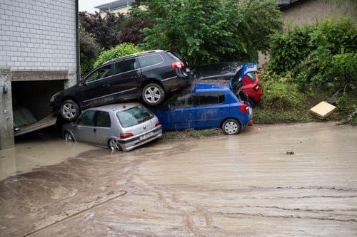 15. Juni: Einen Tag nach dem Hochwasser im thurgausichen Kradolf-Schönenberg wird die Wucht der Wassermassen sichtbar: Autos stehen aufeinander gestapelt vor einer Garage. Bei heftigen Gewittern haben Ablaufrohre die Fluten nicht mehr fassen können. (Bild: Keystone / Gian Ehrenzeller)