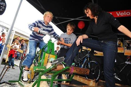 Bei Velo Frank zersägt Julian Barmettler unter den Augen von Samuel Barmettler und Marianne Koch einen Holzstamm. (Bild: Corinne Glanzmann / Neue NZ)