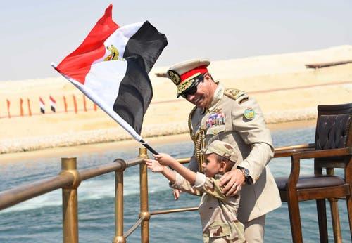 6. August: Der erweiterte Suez-Kanal wird eröffnet. Der neu gebaute Kanal-Abschnitt ermöglicht die gleichzeitige Passage der Schiffe in beide Richtungen. Der ägyptishe Präsident Abdel-Fattah el-Sissi lässt einen Knaben die Fahne schwingen. (Bild: AP / Ägyptisches Präsidium)